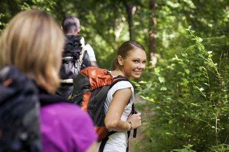 group of man and women during hiking excursion in woods, with woman looking at camera over shoulders and smiling. Waist up photo