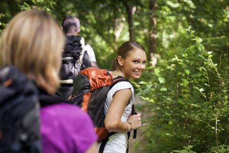 senderismo: grupo de hombres y mujeres durante la excursi�n de senderismo en los bosques, con la mujer mirando a la c�mara sobre los hombros y sonriendo. Medida de la cintura para arriba