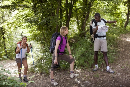 group of man and women during hiking excursion in woods, with woman looking at map and finding direction. Full length photo