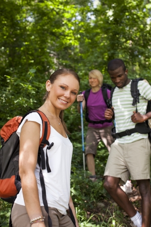 group of man and women during hiking excursion in woods, with woman looking at camera and smiling. Waist up photo