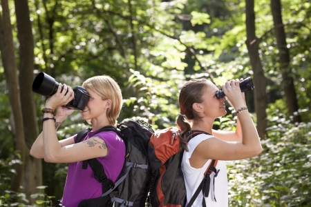 young people trekking among trees and looking at birds with binoculars. Horizontal shape, side view, waist up