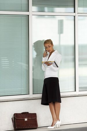 mid adult caucasian business woman talking on mobile phone and reading documents near office building wall. Full length  photo