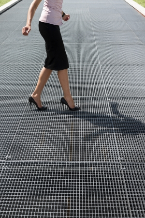 cropped view of mid adult business woman walking on high heels, trying to balance on grating photo