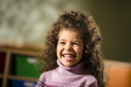 sweater girl: Portraits of children, happy 3 years old female with curly hair smiling for joy in kindergarten