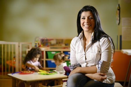 teacher: Portrait of female teacher smiling at camera and happy children eating lunch at school. Copy space Stock Photo