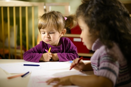 Children having fun at school, two young girls drawing in kindergarten with sad child contemplating her drawing photo