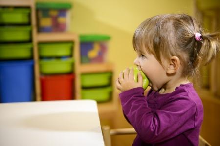 meisje eten: Gelukkige kinderen en gezonde voeding, baby meisje het eten van fruit op school Stockfoto