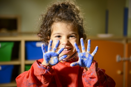 Kids, school and education, happy female child having fun and painting in kindergarten, showing hands to camera photo
