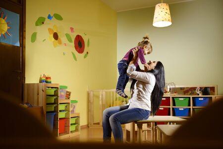 educators: Las personas que se divierten en la escuela, el levantamiento femenino educador el aire hijo en el kinder Foto de archivo