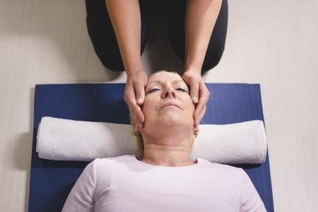 ハイアングルビュー: 代替伝統医学やマッサージ、若い精神ヒーラーの老婆にレイキの治療を行います。ハイアングル、頭と肩