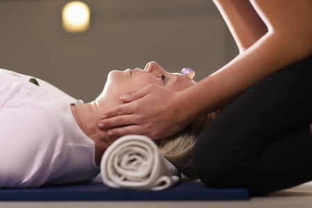 energia espiritual: Reiki terapia con chica trabajando como curandero de esp�ritu, la organizaci�n de cristales y piedras preciosas en el cliente femenino para el tratamiento