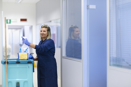 cleaning an office: Women at work, portrait of happy professional female cleaner smiling and looking at camera in office. Three quarter length