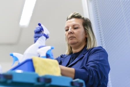 Women at work, portrait of professional female cleaner arranging bottles of detergents on trolley in office Stock Photo