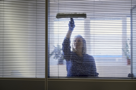Woman at work, professional female cleaner cleaning and wiping window in office with detergent photo