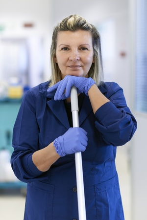 cleaning tools: Women at work, portrait of happy professional female cleaner smiling and looking at camera in office. Three quarter length