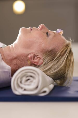 crystal therapy: Senior woman relaxing and lying on pad with amethyst, quartz and other crystals on body. Side view