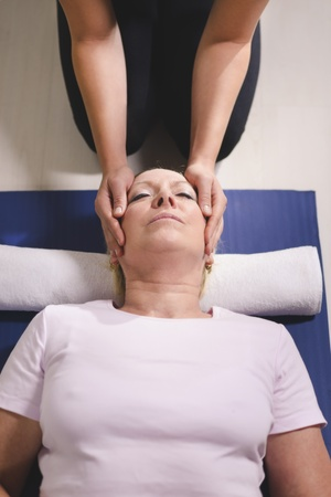 alternative medicine: Alternative traditional medicine and massage, young spirit healer doing reiki treatment to old woman. High angle view, head and shoulders Stock Photo