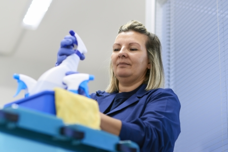 cleaning an office: Women at work, portrait of happy professional female cleaner arranging bottles of detergents on trolley in office Stock Photo