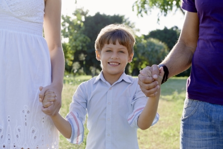 Family fun, happy mother, father and son holding hands in park and looking at camera. Waist up, front view photo