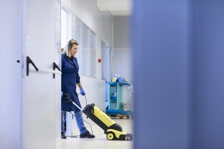 uniformes de oficina: Mujer trabajadora, limpieza profesional de limpieza y lavado de suelo con maquinaria en la construcci�n industrial. De longitud completa, espacio de la copia