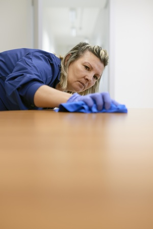 Woman at work, professional maid cleaning desk in office. Copy space photo