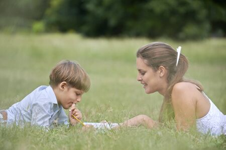 People and education, mother helping child with homework, lying on grass and reading book at park. Medium shot photo