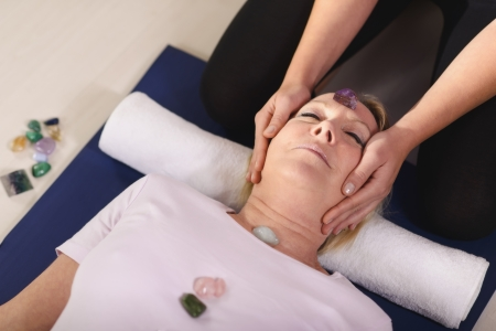 spirituality therapy: Reiki therapy with girl working as spirit healer, arranging crystals and gemstones on female client for treatment Stock Photo