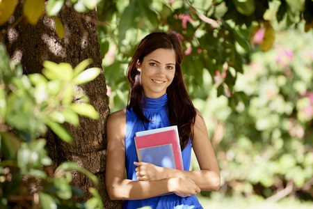 Sequence of students portrait at school, happy young woman smiling with college textbooks in park leaning on tree photo