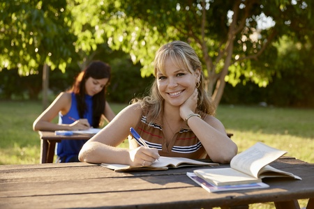 People and education, two young women studying with book for university test in park and smiling at camera photo