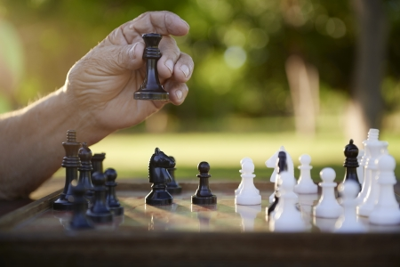 game time: Active retired persons, hand of old man holding chess piece in park. Closeup shot, copy space Stock Photo