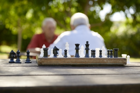 foreground: Active retirement, old friends and leisure, two senior men having fun and playing chess game at park. Focus on chessboard in foreground