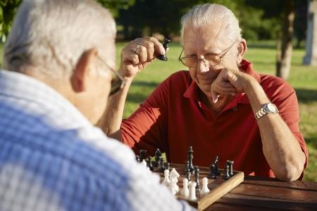 jugando ajedrez: Activos jubilados, viejos amigos y el tiempo libre, dos hombres mayores que se divierten y jugando al ajedrez en el parque. Cabeza y hombros