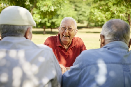 waist up: Active retired senior people, old friends and leisure, group of three elderly men having fun, laughing and talking in city park. Waist up