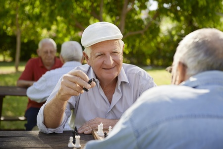 Active retired people, old friends and free time, two seniors\ having fun and playing chess game at park. Waist up