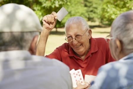 ancianos felices: Jubilaci�n activa, los ancianos y las personas mayores de tiempo libre, grupo de tres hombres de edad avanzada que se divierte y que juega en el parque de tarjetas de juego