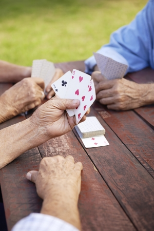 games hand: Active retirement, old people and seniors free time, group of three elderly men having fun and playing cards game at park