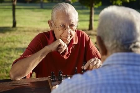 ajedrez: Activos jubilados, viejos amigos y el tiempo libre, dos hombres mayores que se divierten y jugando al ajedrez en el parque. Cabeza y hombros