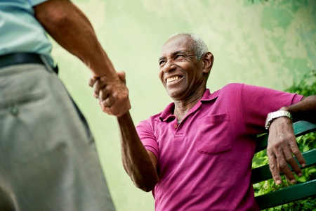 shaking: retired elderly people and free time, happy senior african american and caucasian male friends greeting and sitting on bench in park Stock Photo