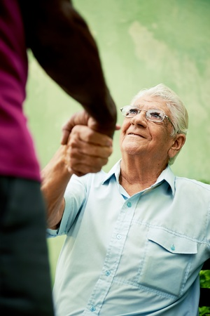 retired elderly people and free time, happy senior african american and caucasian male friends greeting and sitting on bench in park Stock Photo