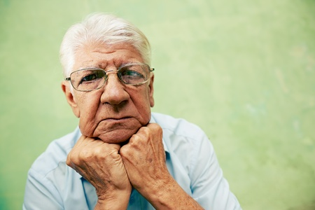 people and emotions, portrait of depressed senior hispanic man with glasses looking at camera, leaning with hands on chin. Copy space photo