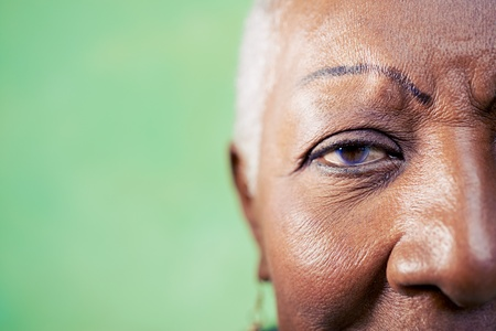 Old black woman portrait, close-up of eye and face on green background. Copy space photo