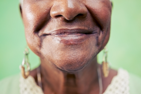 feeling up: Old black woman portrait, close-up of eye and face on green background. Copy space Stock Photo