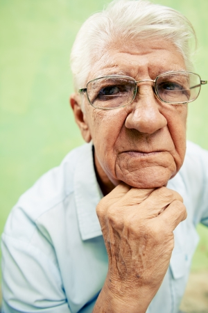 people and emotions, portrait of depressed senior hispanic man with glasses looking at camera, leaning with hands on chin photo