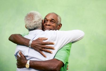 familia abrazo: Activos jubilados de edad y de ocio, dos hermanos negros altos abrazando al aire libre