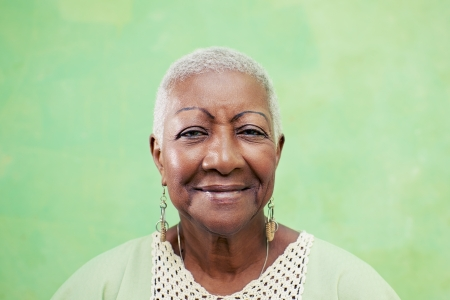 Old black woman portrait, lady in elegant clothes smiling on green background. Copy space photo