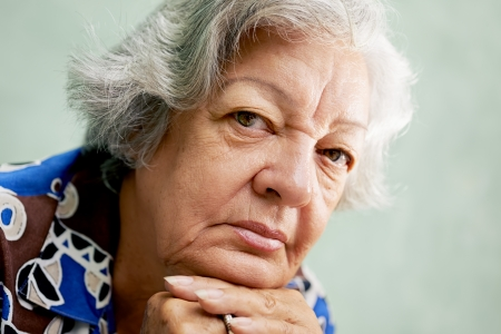 people and emotions, portrait of depressed senior hispanic woman with white hair looking at camera, leaning with hands on chin photo