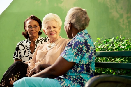 senior female: Active retired elderly women and free time, group of happy senior african american and caucasian female friends talking and sitting on bench in park Stock Photo