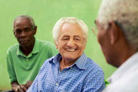 retired: retired elderly people and free time, group of happy senior african american and caucasian male friends talking and sitting on bench in park Stock Photo