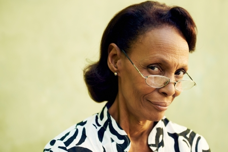 Senior people and confidence, portrait of proud african american woman with glasses smiling and looking at camera. Copy space photo