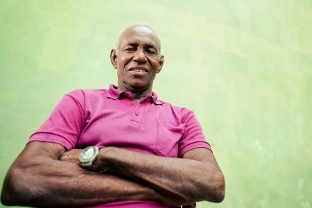 Les personnes âgées et les émotions, portrait de hauts homme afro-américain regardant et souriant à la caméra, les bras croisés. L'espace de copie, faible angle de vue,